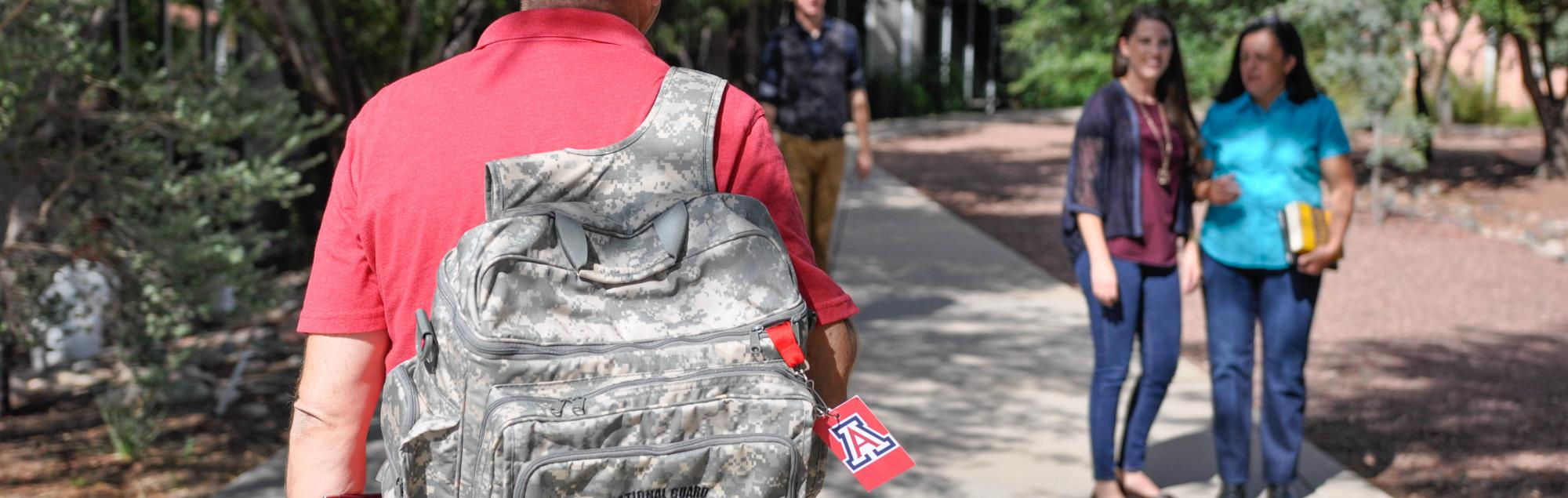 UA student walking with army backpack